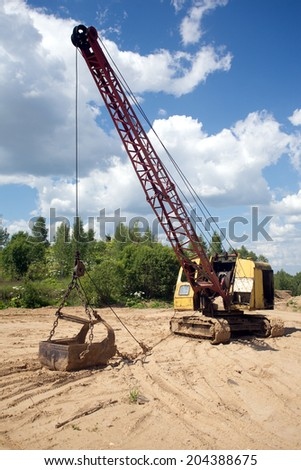 Yellow excavator with big heavy bucket standing on sand on background of forest and blue sky with white clouds on summer day