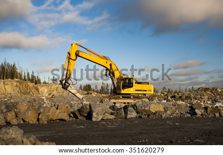 Yellow excavator with hydraulic hammer is working in gravel pit in sunny day.
