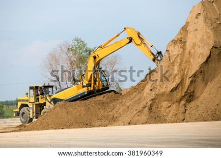 Yellow  excavator working digging in sand quarry - stock photo