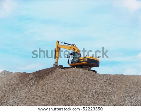 Yellow Excavator working on a mountain of rubble - stock photo