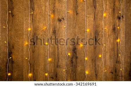 Yellow fairy lights on a wooden wall - holyday background. - stock photo