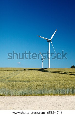 yellow field and wind two wind turbines