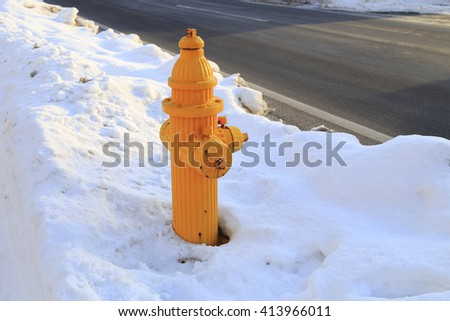 Yellow Fire Hydrant  over white snow along the road - stock photo