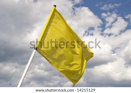 Yellow flag on a background of the dark blue sky with clouds. - stock photo