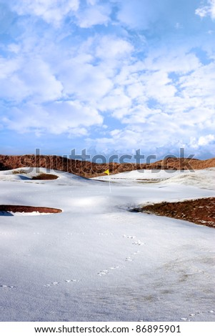 yellow flag on a snow covered links golf course in ireland in winter
