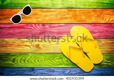 Yellow flip flops and sunglasses on a color wooden background - stock photo