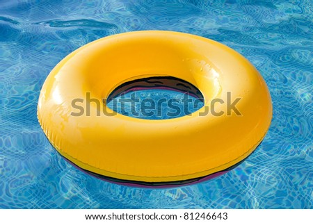 Yellow float floating in the pool with blue water - stock photo