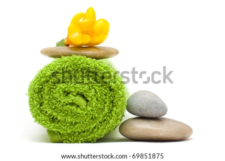 Yellow flower, green towel and river stones - harmony spa concept - stock photo