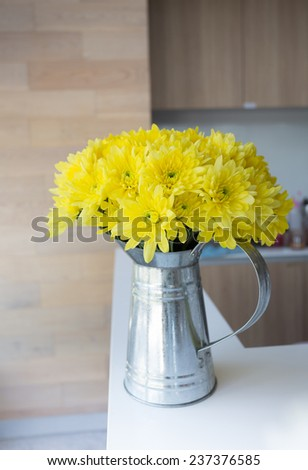 yellow flower in aluminum vase on the table at wooden kitchen