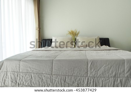 Yellow flower in flower pot on gray bed at bedroom.