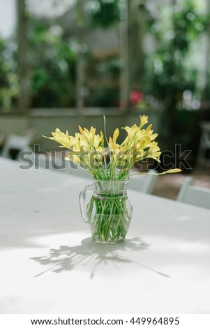 Yellow flower in glass vase on wooden table. Selective focus - stock photo