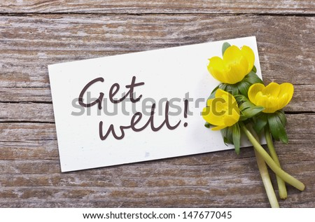 yellow flowers and white card with lettering get well/get well/flowers - stock photo