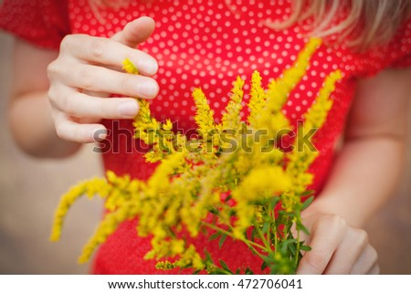 yellow flowers in hans of young lady in red dress