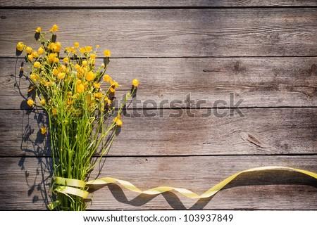 yellow flowers on wooden background - stock photo