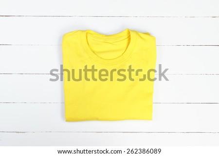 Yellow folded t-shirt on white wooden background - stock photo