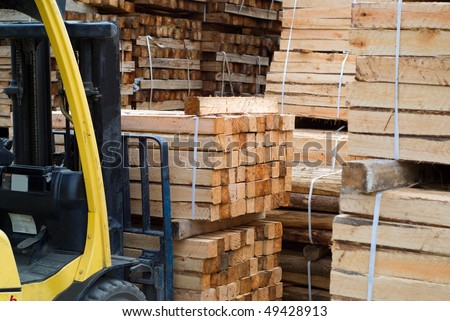 Yellow folk lift truck in wood factory or forestry timber depot - stock photo