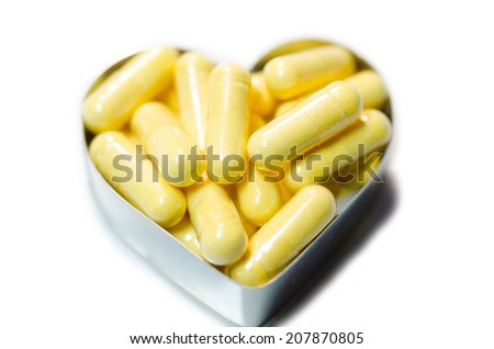 yellow food supplemnet CoQ10 (Co-enzyme Q10) capsules in heart shape box closeup on white background isolated - stock photo