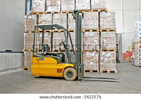 Yellow fork lifter truck and cargo boxes - stock photo