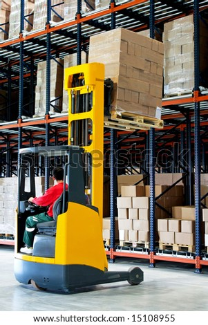 Yellow fork lifter with pallet in warehouse - stock photo