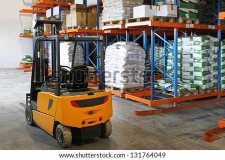 Yellow forklift in distribution warehouse with sacks