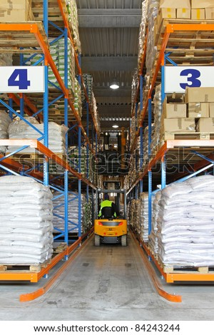 Yellow forklift in warehouse between shelves - stock photo