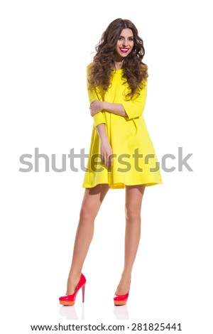 Yellow Fresh Dress. Smiling fashion model posing in red high heels and yellow mini dress. Full length studio shot isolated on white. - stock photo