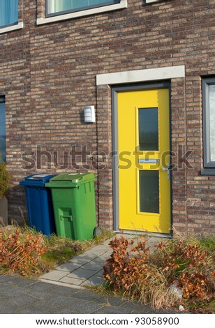 yellow front door and a blue and green trash can for separate trash - stock photo