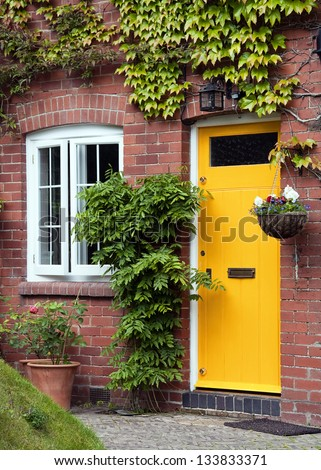 Yellow front door entrance and old style window of a red brick house or a cottage with hanging flower basket and green ivy. - stock photo