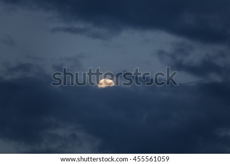 Yellow full moon night with dark clouds - stock photo