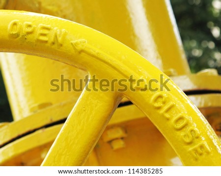 Yellow gas pipeline valve open ,two ways arrow, close signs closeup - stock photo