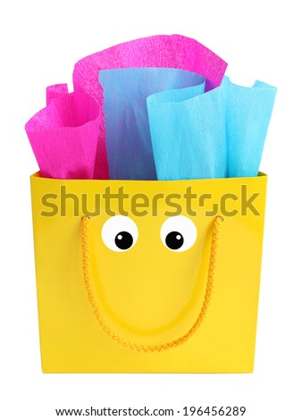 Yellow gift bag stuffed with pink and turquoise tissue paper with a smiley face on it, isolated on white - stock photo