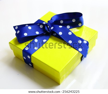 yellow gift box and blue dotted ribbon isolated over white - stock photo