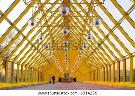Yellow glass corridor in bridge and people walking - stock photo