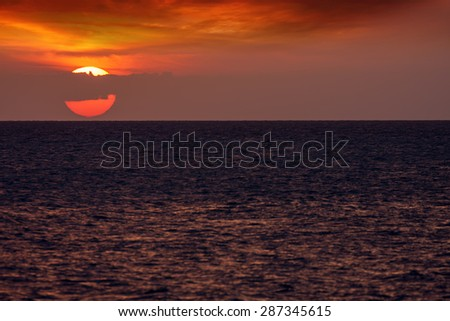 yellow glow of the rising or setting sun over a textured ocean showing the yellow orb of the sun on the horizon - stock photo