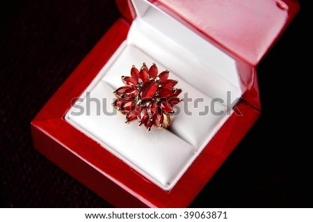 Yellow gold garnet ring in a jewelry box - stock photo