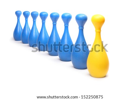 Yellow (golden) bowling pin among common blue pins. Leadership metaphor. - stock photo