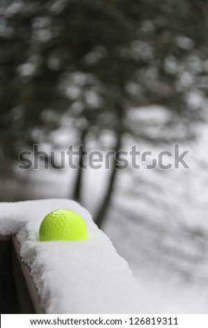 Yellow golf ball in snow on ledge in winter (selective focus) - stock photo