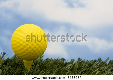 Yellow golf ball on tee with sky background