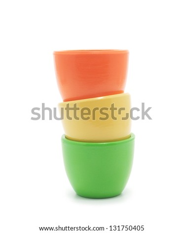 yellow, green and orange ceramic cup placed one inside the other. Isolated on white background.
