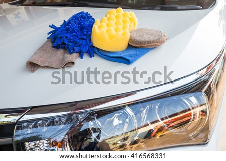 Yellow, green sponges and blue mitts for washing and microfiber fabric with cleaner cloth on white car - stock photo