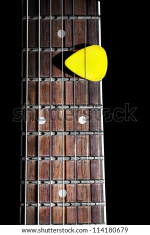 Yellow guitar pick on the fingerboard close up isolated on black background - stock photo