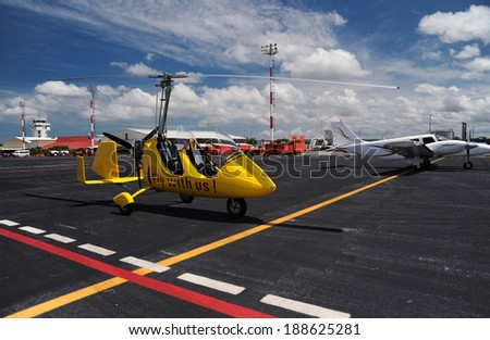 Yellow gyroplane parked on the apron in the international airport