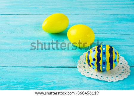 Yellow hand-painted Easter eggs on blue wood plank. Easter background. Easter symbol. Copy space - stock photo