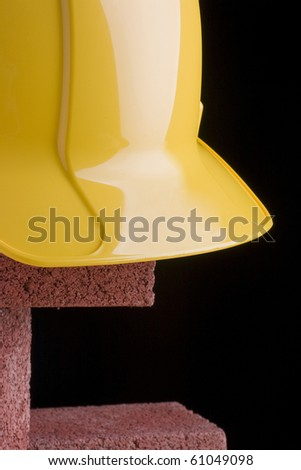 Yellow hard hat and red bricks on a black background. - stock photo