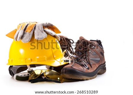 Yellow hard hat of the builder, goggles, gloves and boots on a white background - stock photo