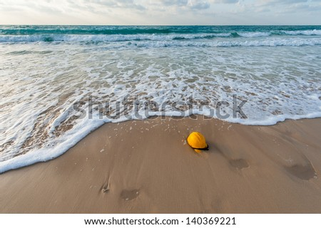 Yellow hard hat on the coast , garbage and urbanization polluting the natural environment - stock photo