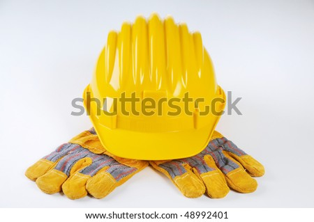 Yellow hard hat on the working gloves - stock photo