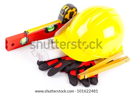 yellow hard hat, tools and construction plans on white background