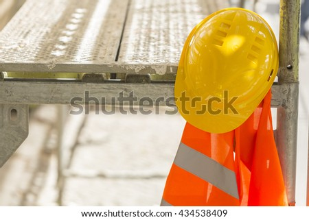 Yellow hardhat and safety vest on scaffolding
