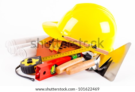 yellow hardhat, brick  tools and construction plans on white background - stock photo